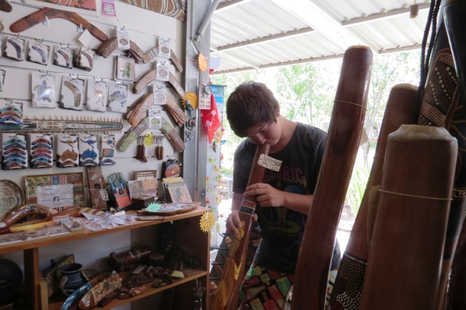 Adam at the Eumundi Markets, being instructed on how to play the didgeridoo.