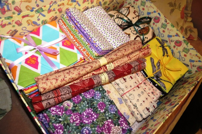 """Quilting 'fat-quarters"""" all neatly arranged in a sewing storage box."""