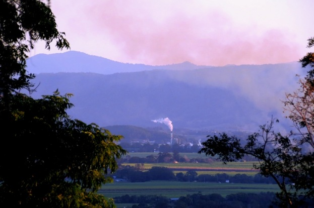 The sugar mill in the valley, surrounded by cane fields.